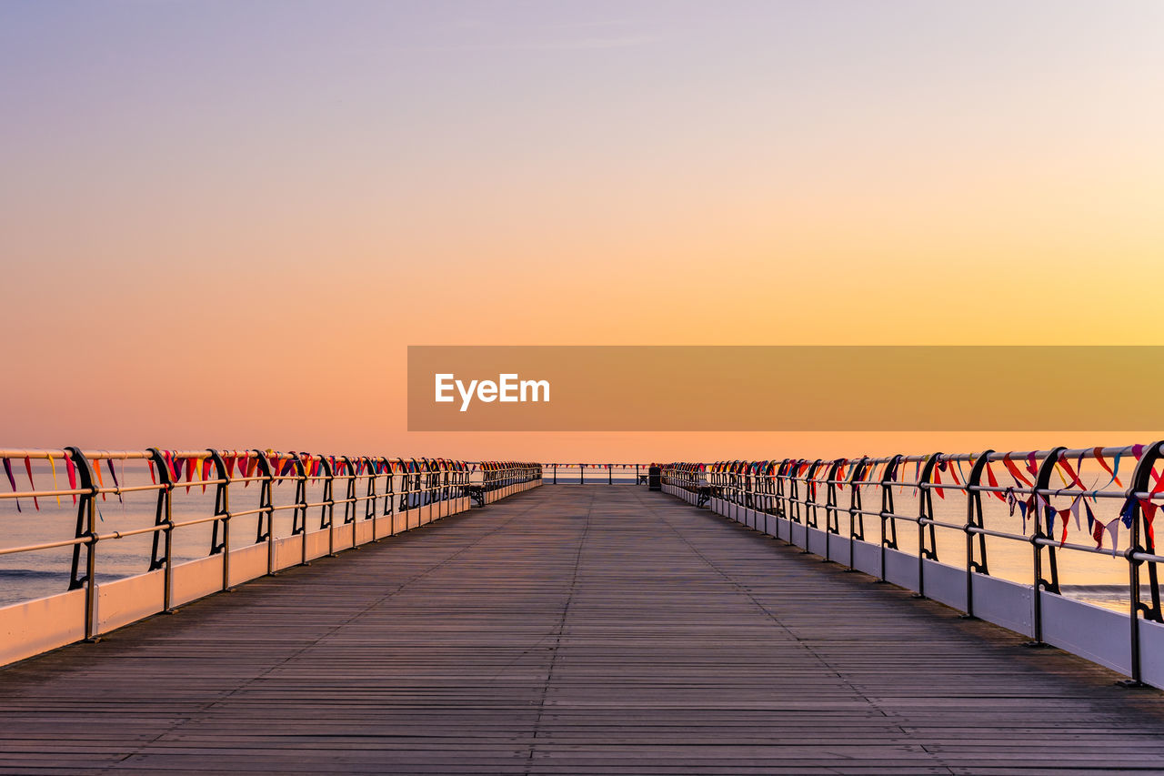 sunset, sky, orange color, railing, diminishing perspective, direction, the way forward, clear sky, copy space, nature, beauty in nature, bridge, connection, in a row, sea, built structure, outdoors, scenics - nature, no people, tranquility