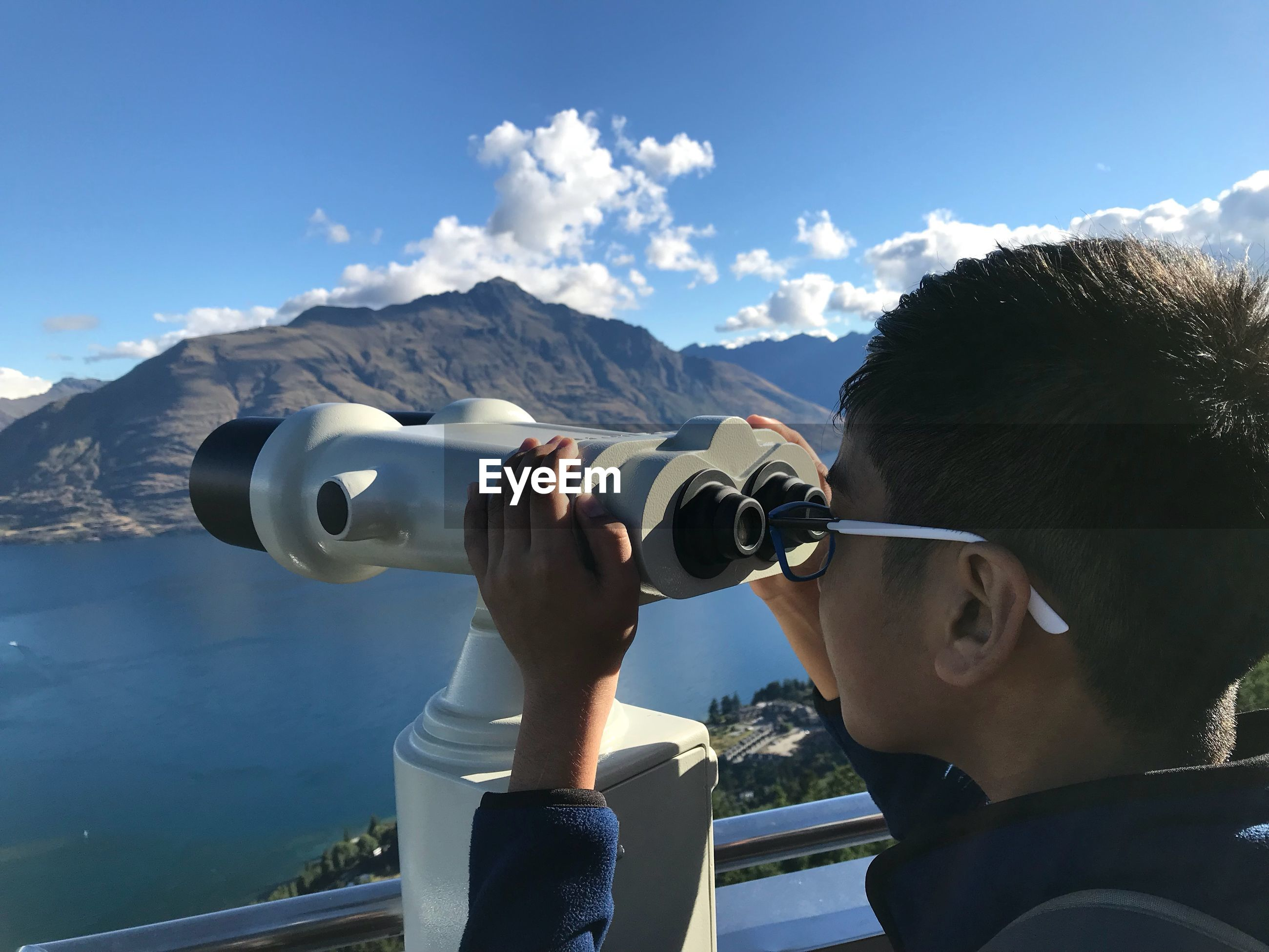 Close-up of boy looking through coin-operated binoculars against valley