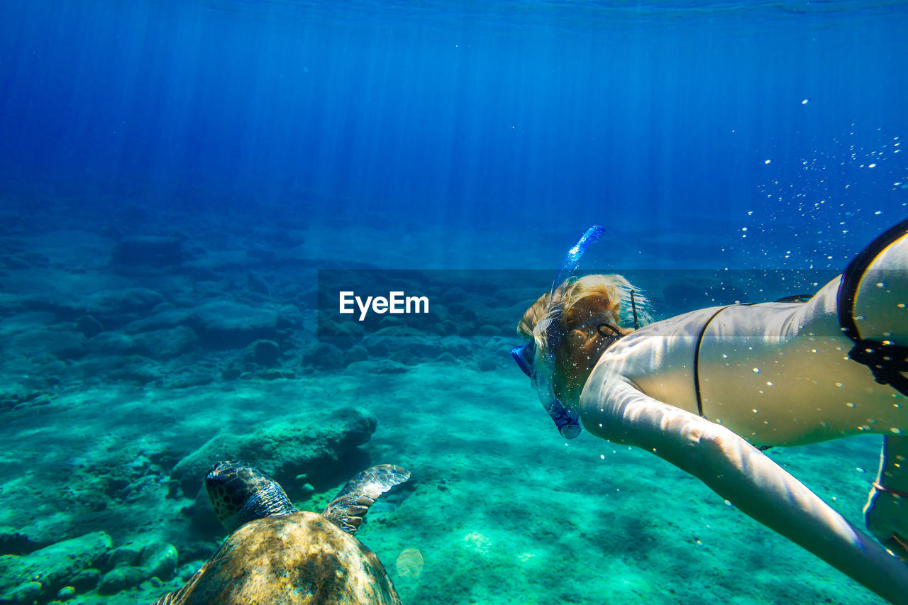 Close-Up Of Mature Woman Swimming Undersea With Turtle
