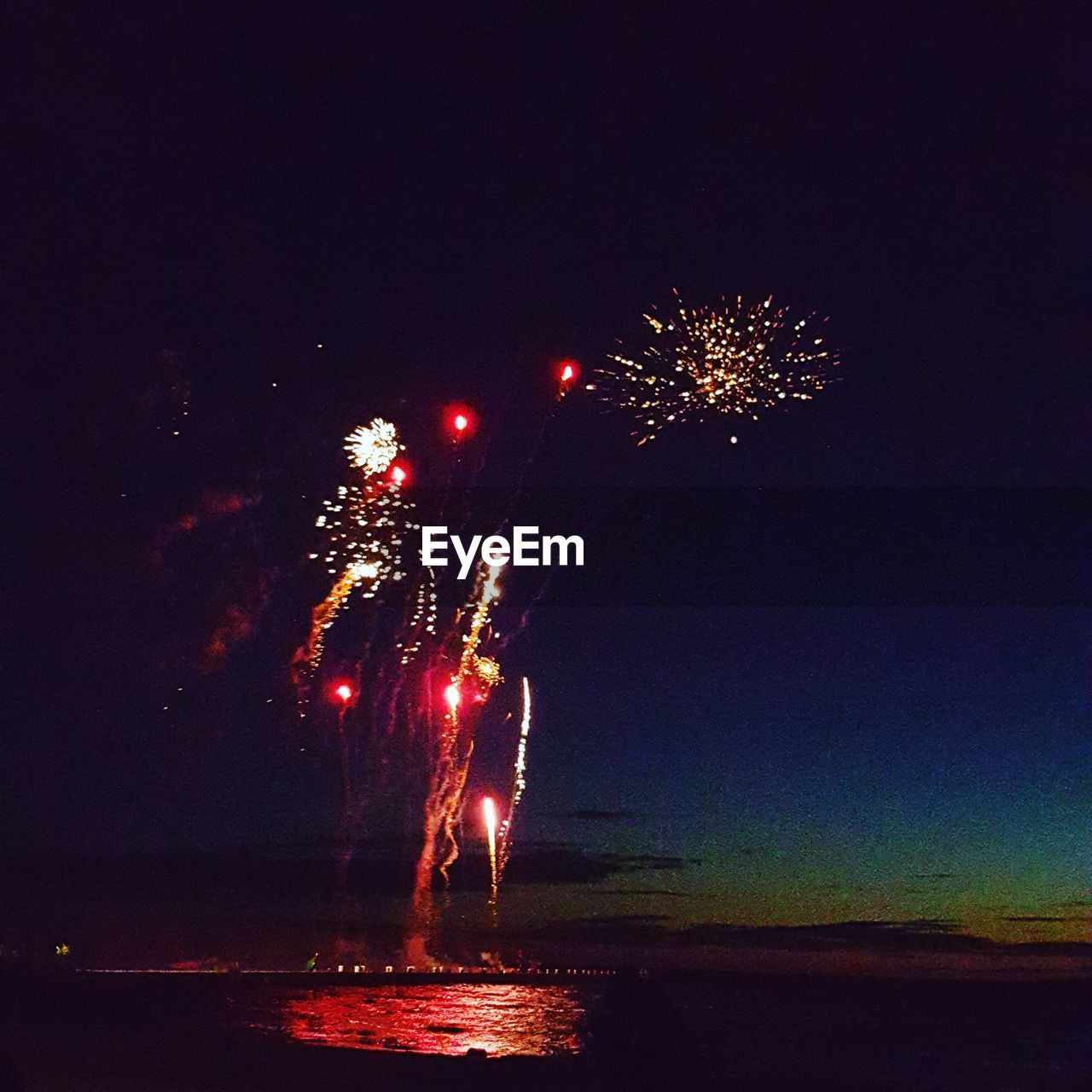 night, celebration, firework display, firework - man made object, arts culture and entertainment, exploding, illuminated, event, long exposure, glowing, blurred motion, motion, firework, low angle view, multi colored, outdoors, sky, no people, water