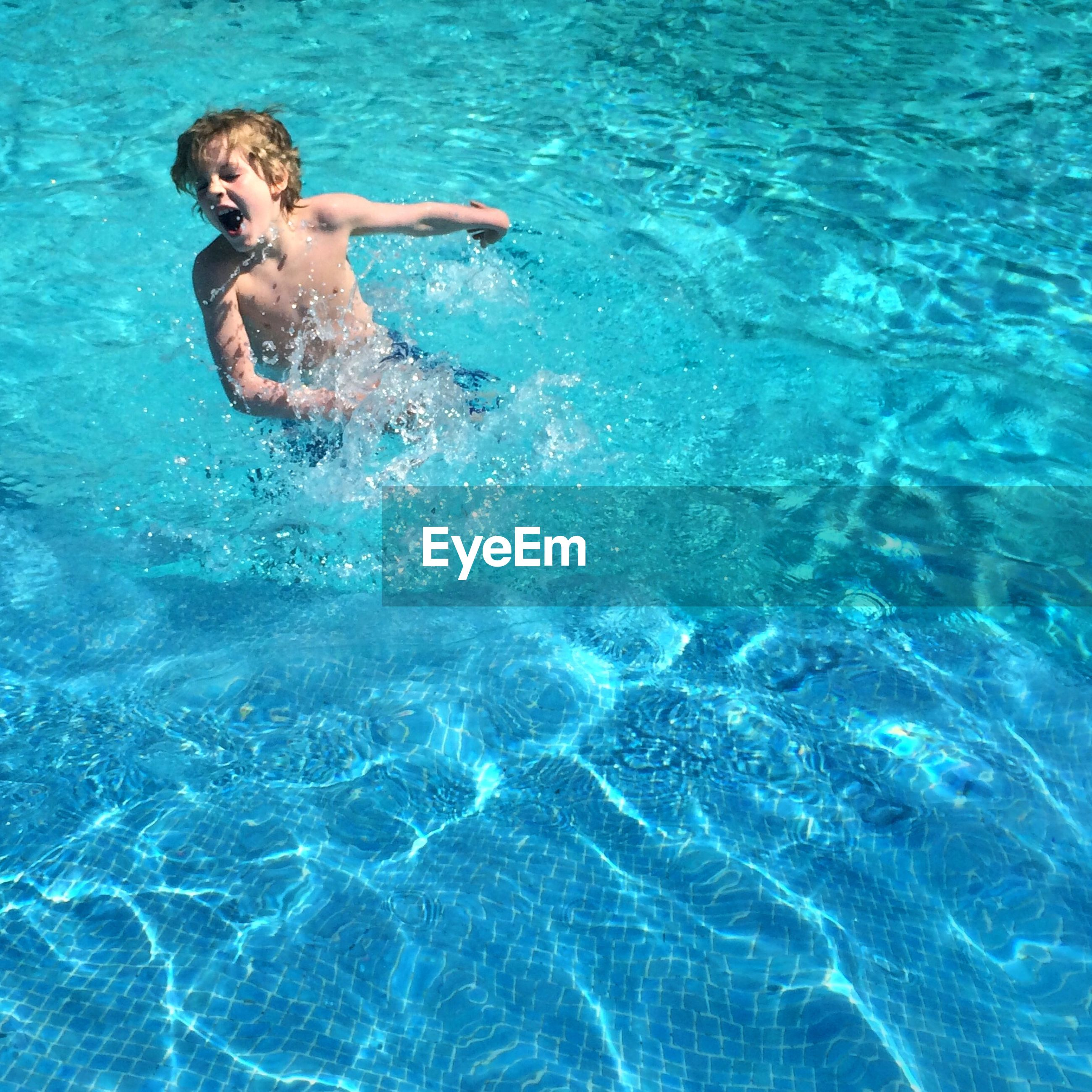 High angle view of boy playing in swimming pool