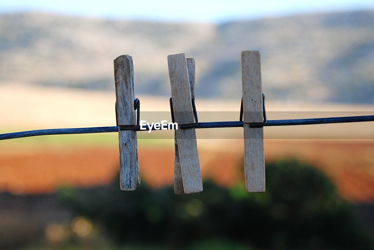 Close-Up Of Clothespins Hanging On String