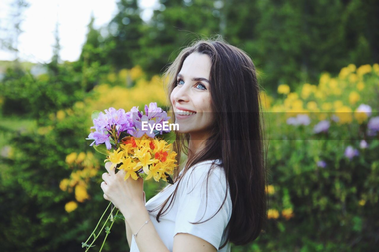 Beautiful Woman Looking Away While Holding Flowers