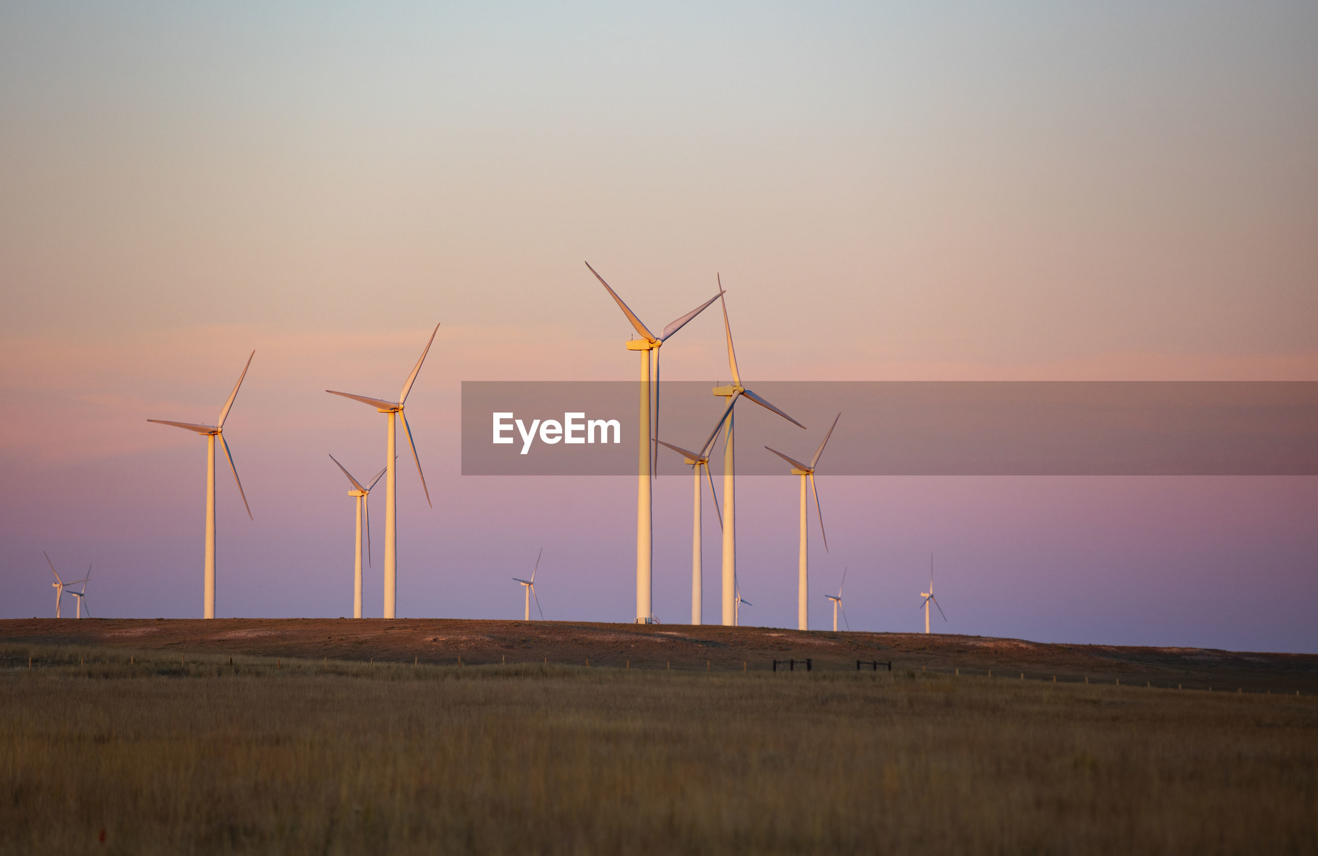 WINDMILLS ON FIELD AGAINST SKY AT SUNSET