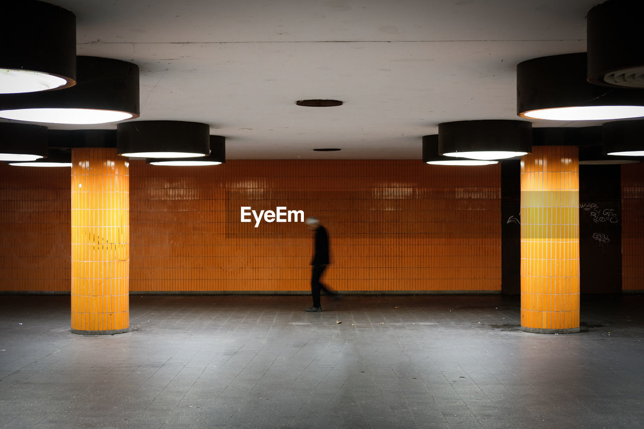 architecture, illuminated, indoors, lighting equipment, walking, one person, built structure, subway, full length, public transportation, transportation, architectural column, ceiling, flooring, rear view, sign, real people, direction, orange color, light fixture, light, underpass, underground walkway