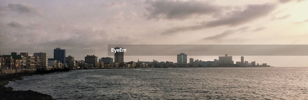 architecture, skyscraper, cityscape, building exterior, city, sky, built structure, urban skyline, waterfront, no people, sea, modern, outdoors, water, day, nature