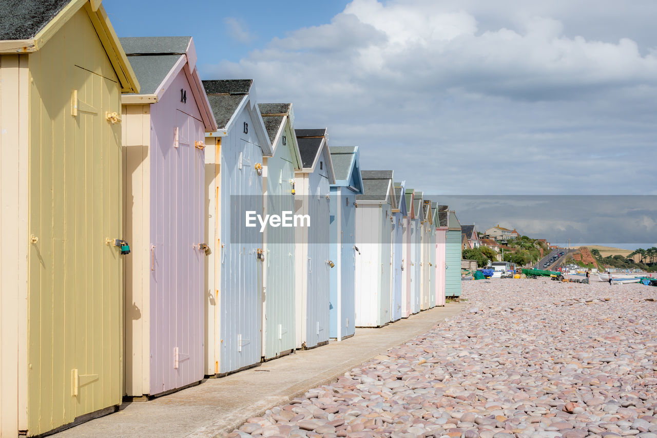 built structure, cloud - sky, architecture, sky, building exterior, beach hut, in a row, day, nature, building, beach, hut, land, no people, outdoors, side by side, entrance, house, direction, door