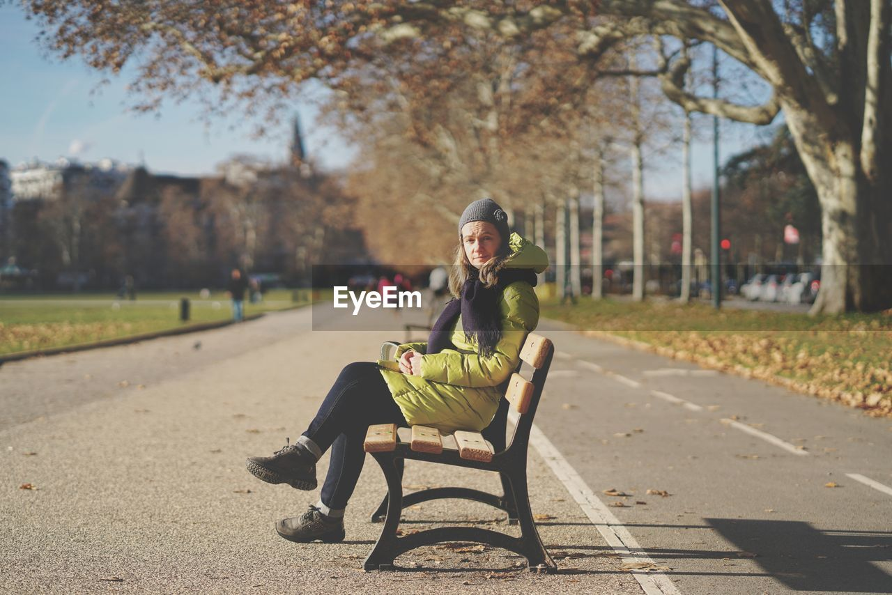 full length, one person, real people, sitting, tree, lifestyles, nature, leisure activity, park, plant, focus on foreground, portrait, looking at camera, day, sunlight, park - man made space, casual clothing, seat, transportation, outdoors