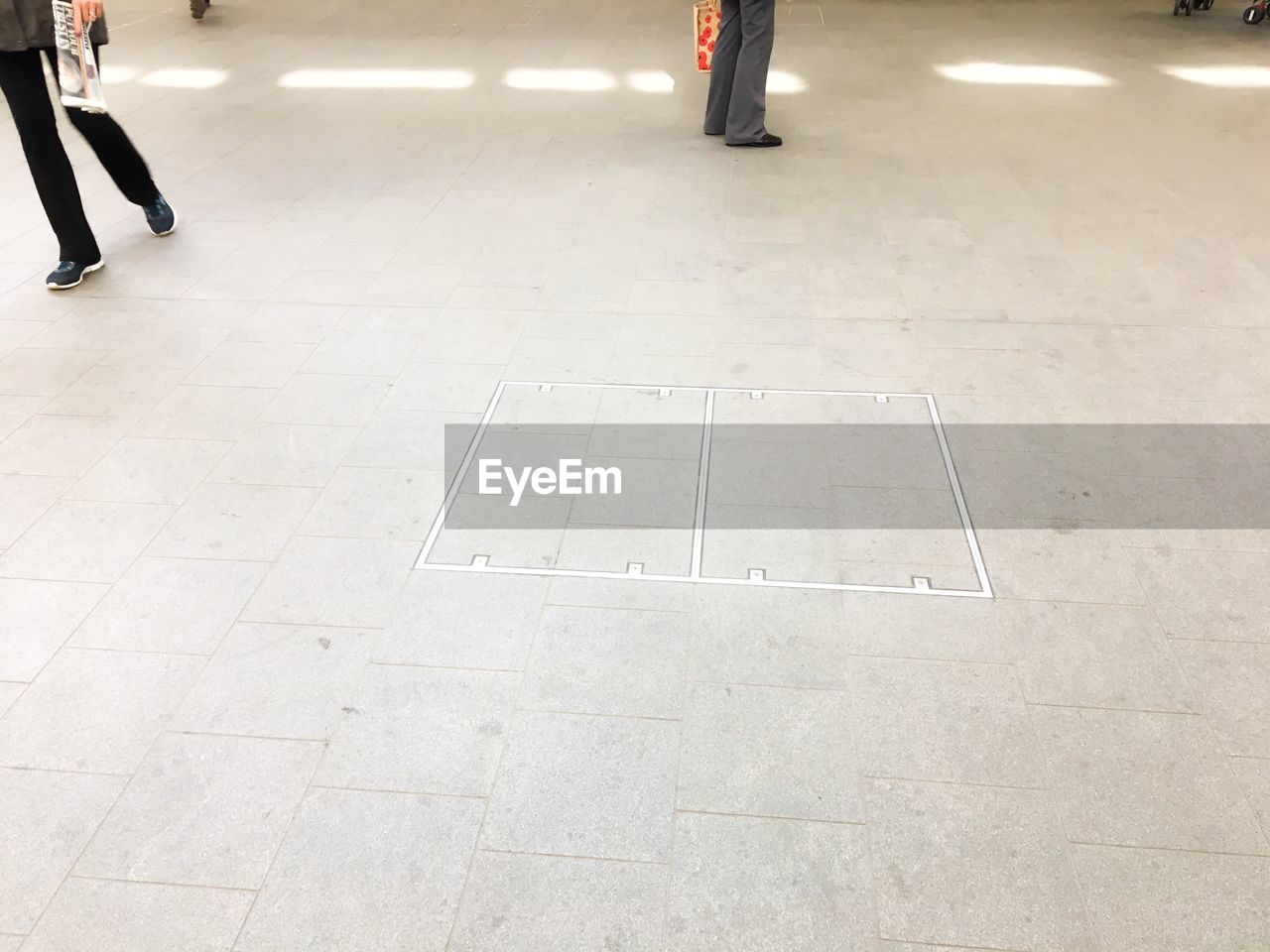 flooring, city, day, transportation, real people, outdoors, sign, high angle view, low section, symbol, street, incidental people, lifestyles, road, architecture, human leg, road marking, tile, travel, leisure activity, tiled floor, waiting