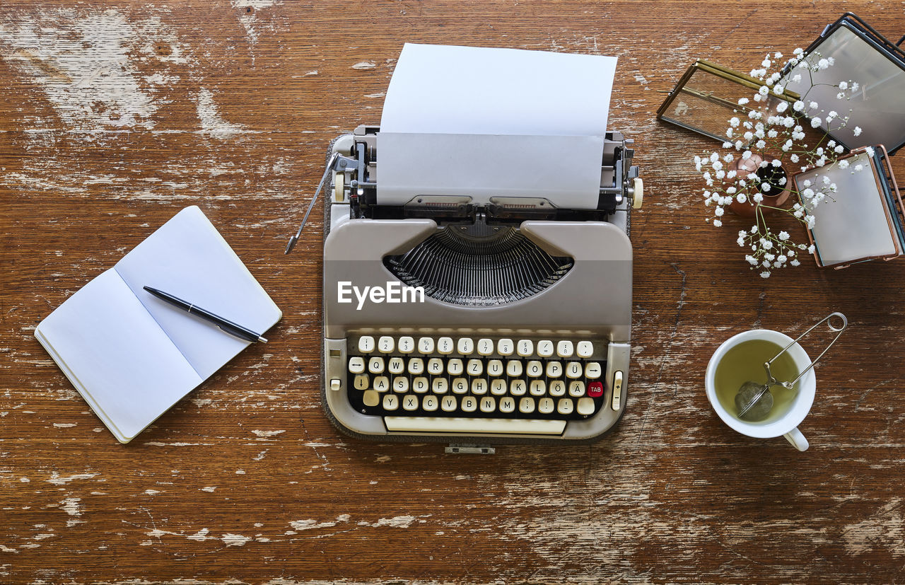 table, high angle view, still life, technology, indoors, communication, typewriter, paper, no people, cup, wood - material, food and drink, retro styled, drink, coffee - drink, wireless technology, mug, coffee, coffee cup, keyboard