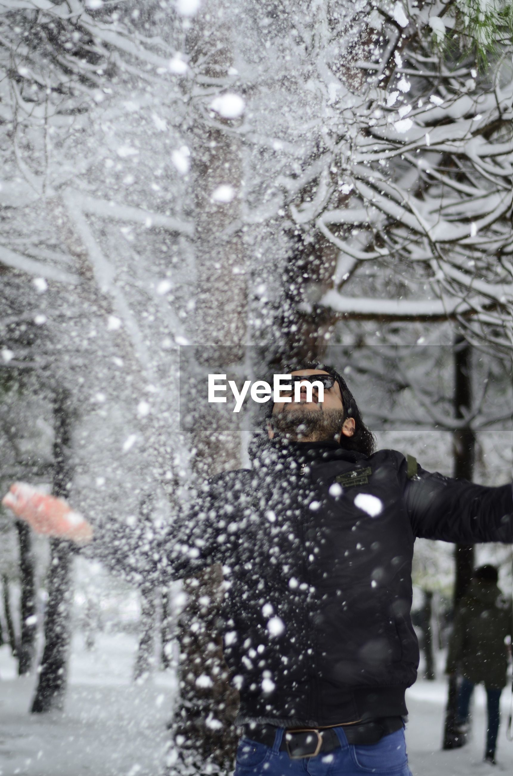 Reflection of man in snow covered tree