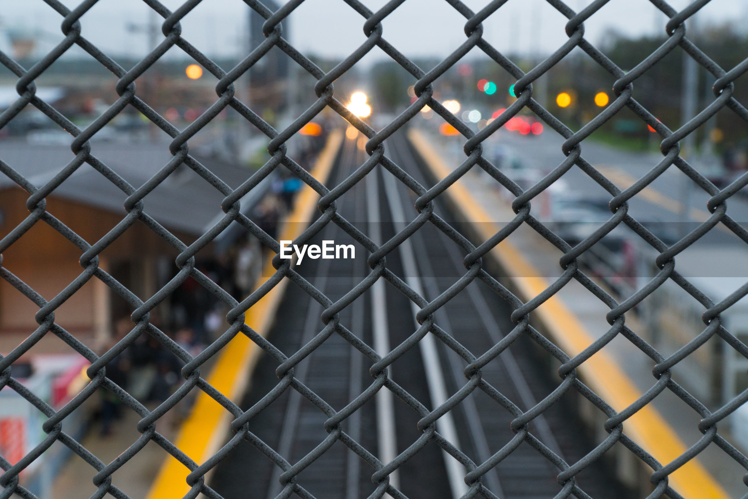 FULL FRAME SHOT OF CHAINLINK FENCE WITH HIGHWAY IN BACKGROUND