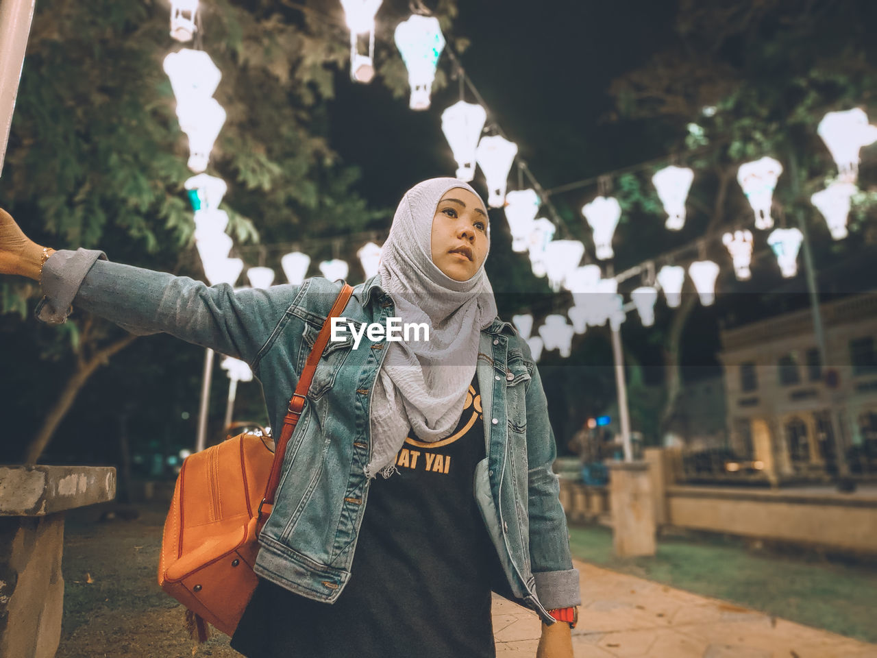 Woman standing against illuminated lights at night