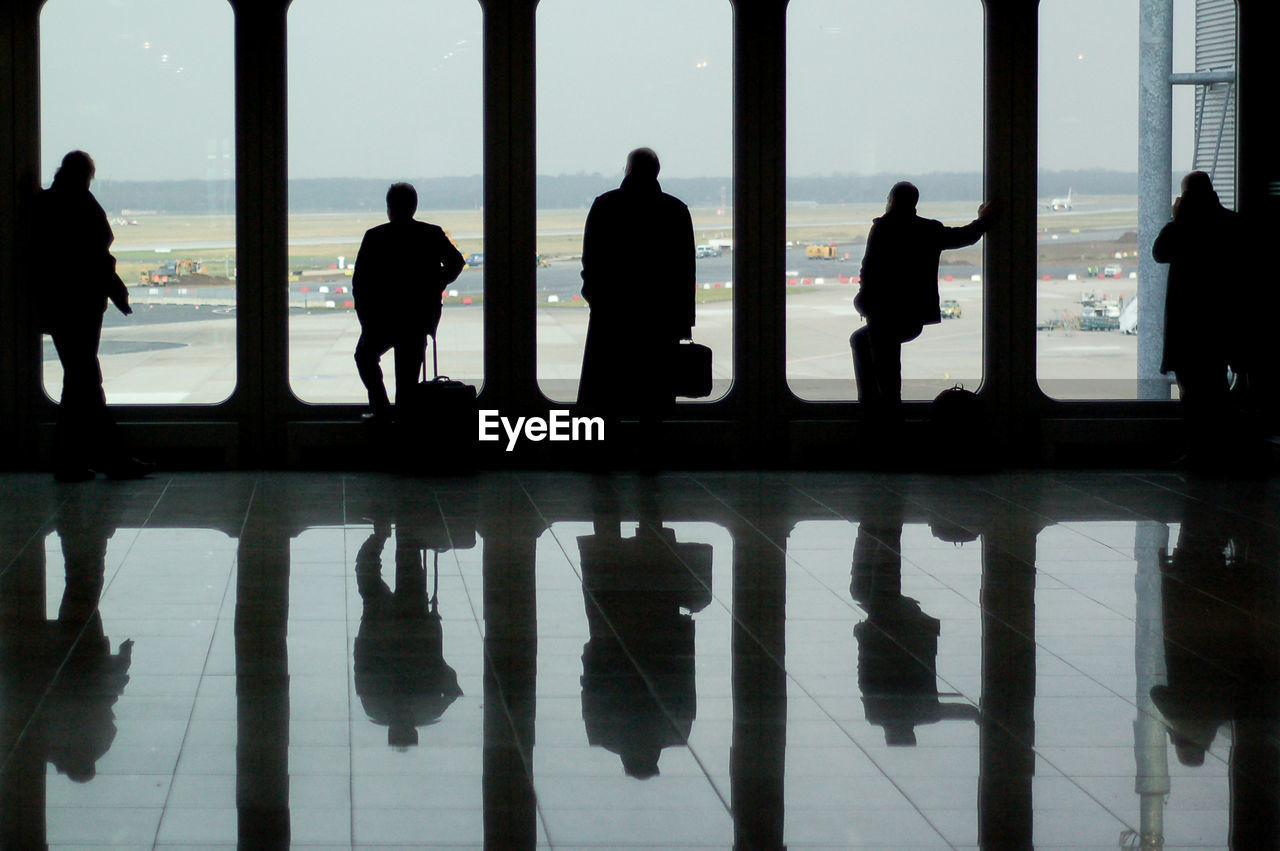silhouette, group of people, reflection, real people, men, architecture, walking, glass - material, people, window, flooring, city, day, built structure, lifestyles, transparent, outdoors, travel, standing, nature, waiting