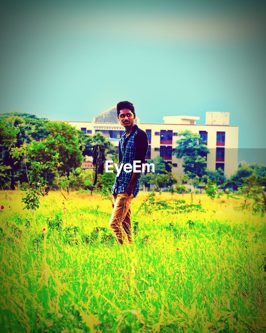 young adult, front view, standing, one person, real people, field, portrait, grass, casual clothing, young men, looking at camera, young women, clear sky, full length, outdoors, lifestyles, day, nature, leisure activity, green color, smiling, building exterior, built structure, happiness, architecture, tree, sky, people