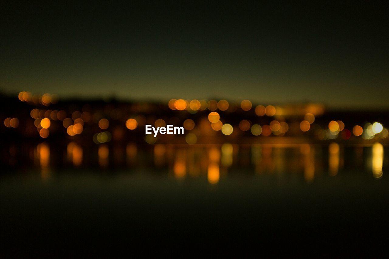Defocused image of town by lake at dusk
