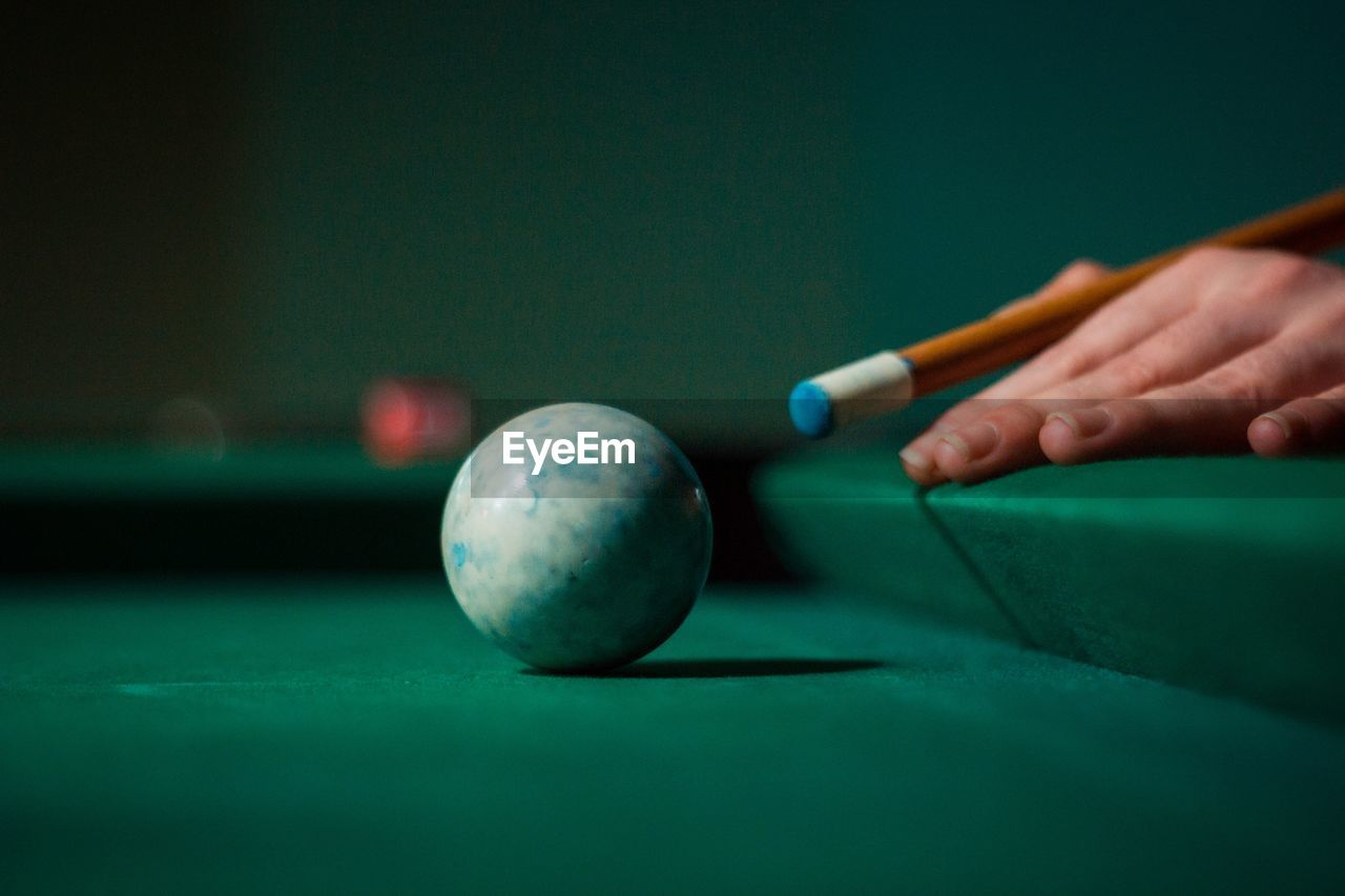 ball, hand, human hand, sport, pool ball, pool table, leisure activity, pool - cue sport, green color, pool cue, table, human body part, snooker, one person, skill, indoors, sphere, playing, accuracy, holding
