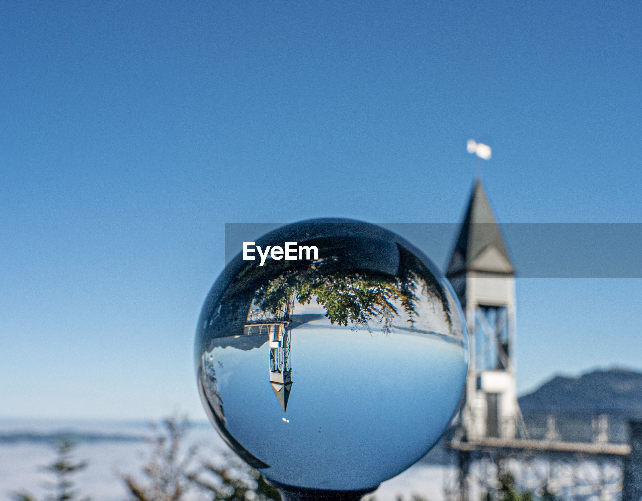 CLOSE-UP OF CRYSTAL BALL AGAINST BLUE SKY WITH REFLECTION