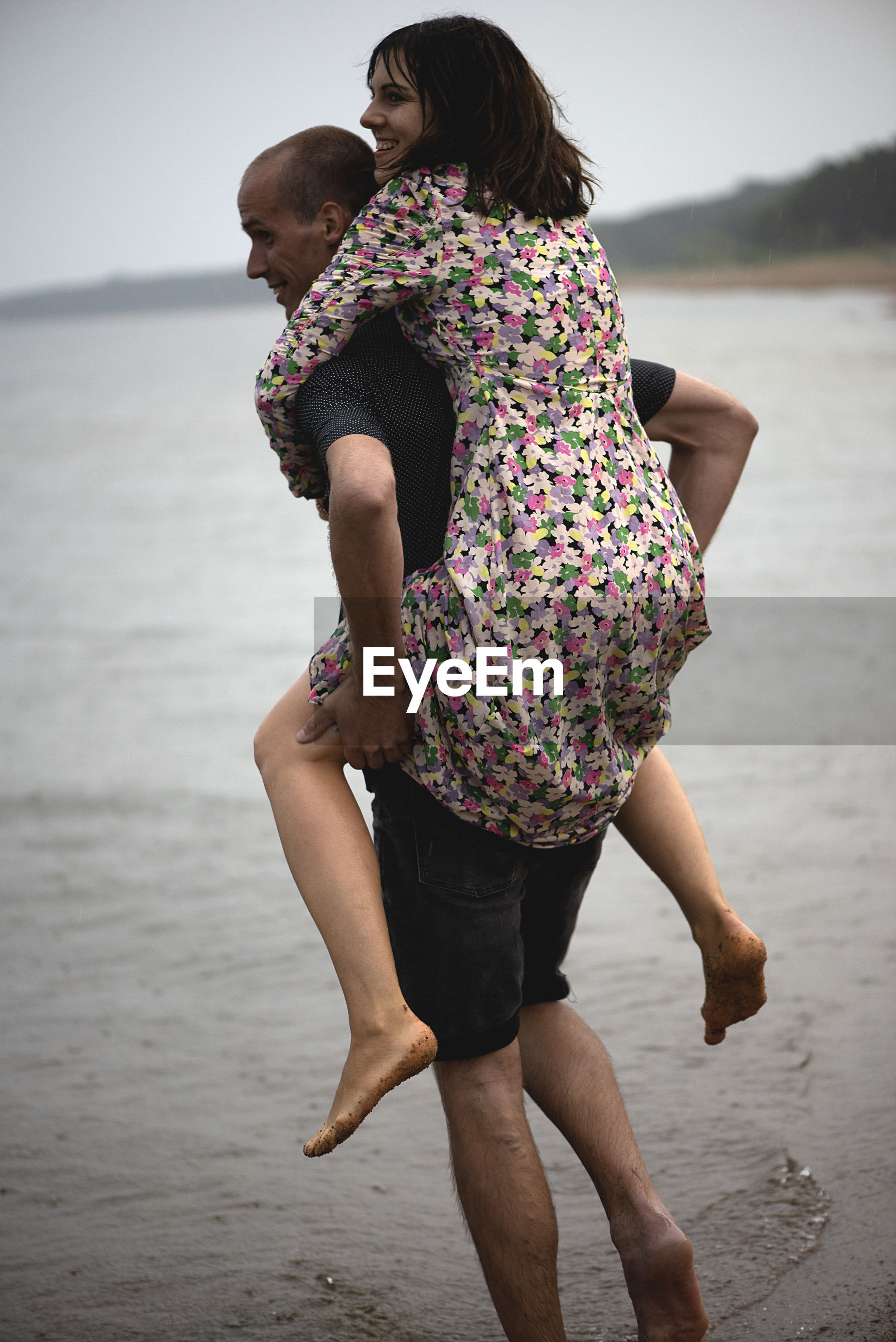 Young couple having fun on the beach at rainy summer day,a man carries a woman on his shoulders
