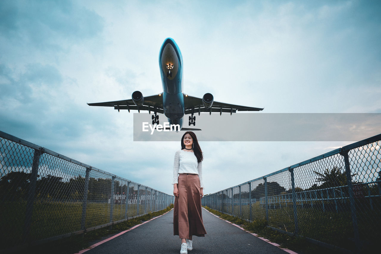 sky, one person, cloud - sky, real people, casual clothing, lifestyles, front view, full length, transportation, standing, leisure activity, day, nature, young adult, three quarter length, fence, young women, outdoors, airplane, teenager