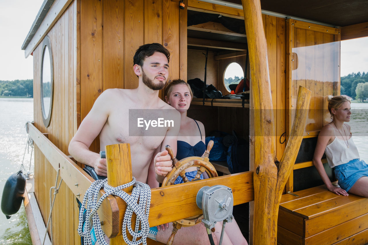 real people, shirtless, leisure activity, lifestyles, standing, three quarter length, wood - material, young adult, young men, men, day, sitting, looking at camera, women, people, togetherness, smiling, males, adult, couple - relationship