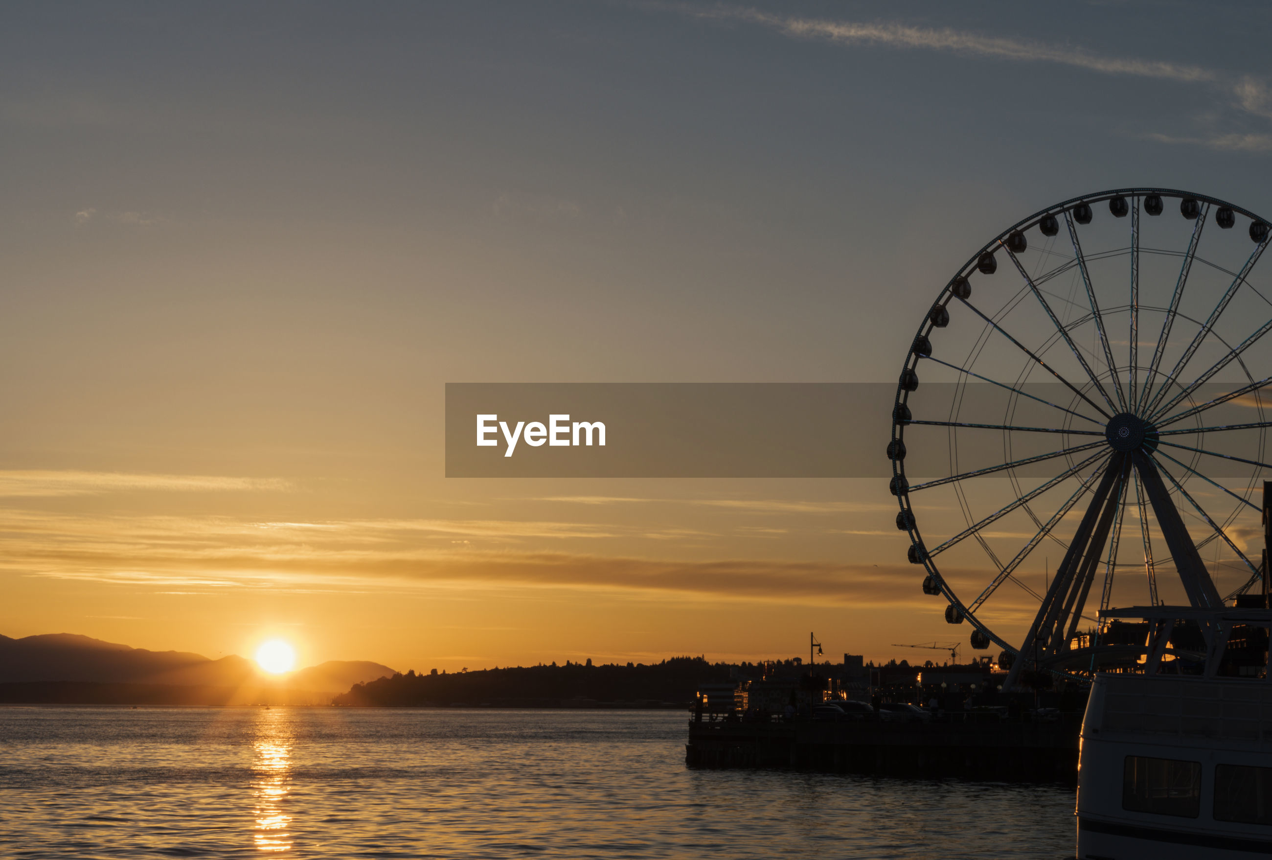 Silhouette ferris wheel by sea against sky during sunset