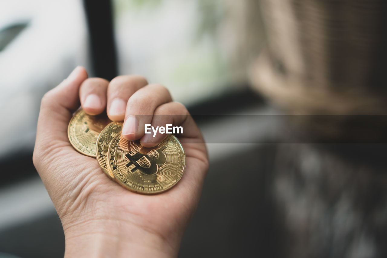 Cropped hand of person holding bitcoins
