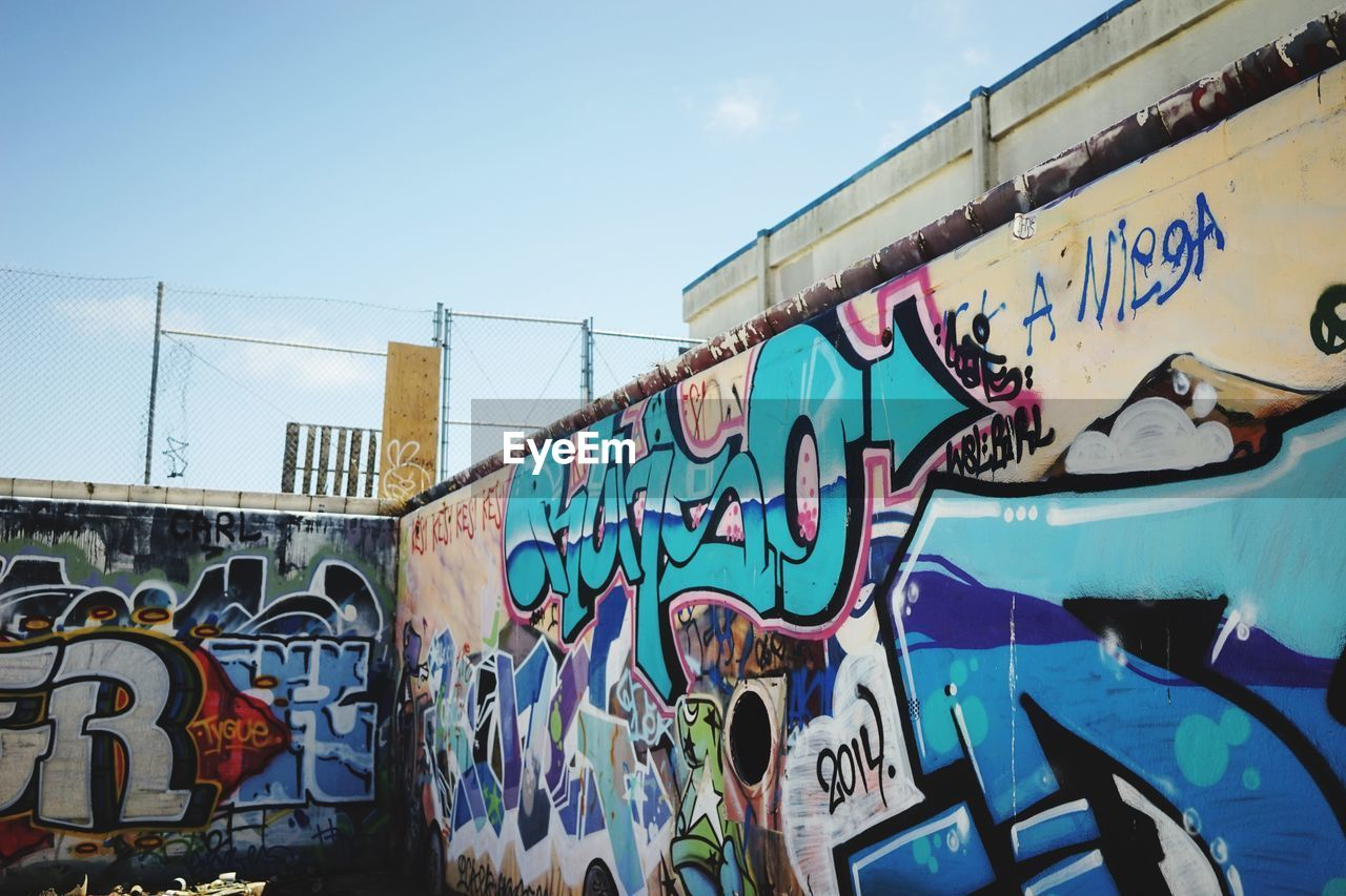 LOW ANGLE VIEW OF GRAFFITI WALL AGAINST SKY