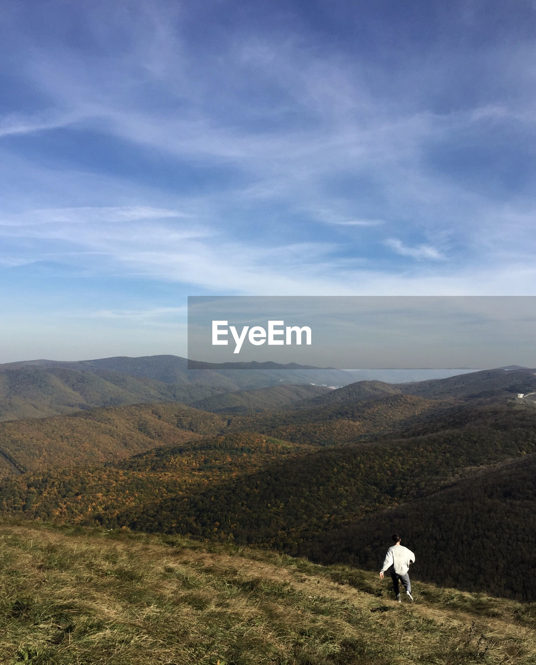 Rear view of hiker walking on mountain against cloudy sky