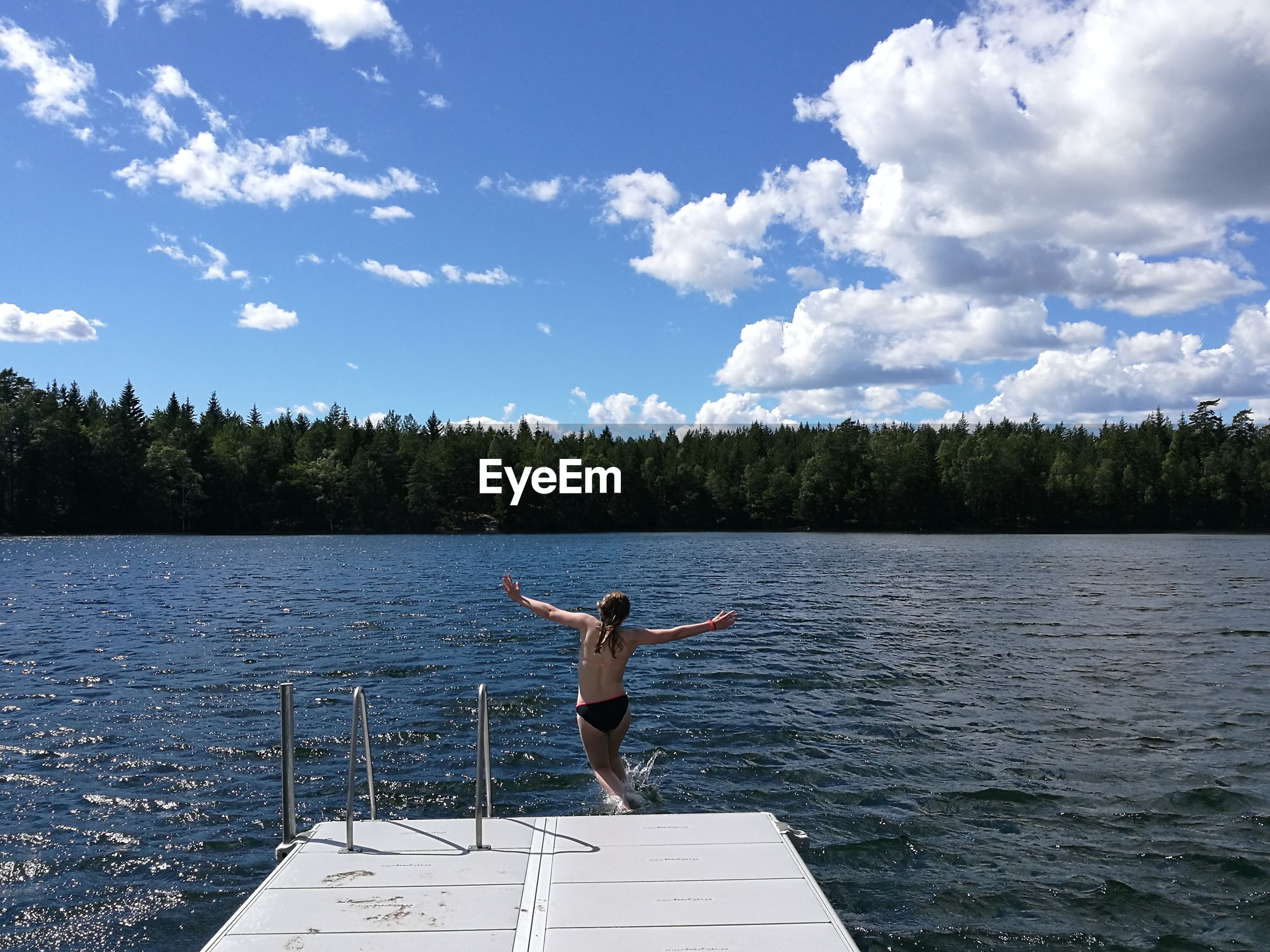 Shirtless girl diving into lake against blue sky