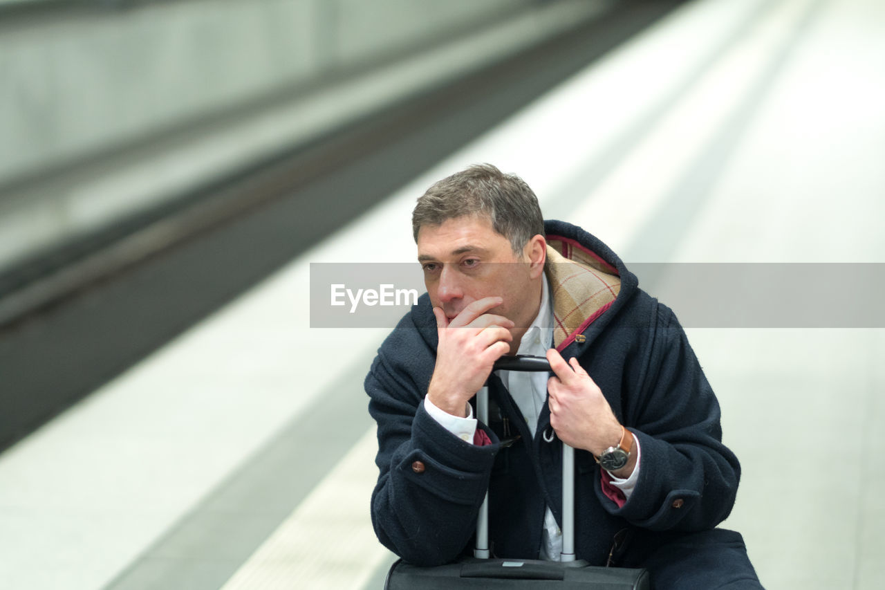 Man with hands covering mouth sitting at railroad station platform