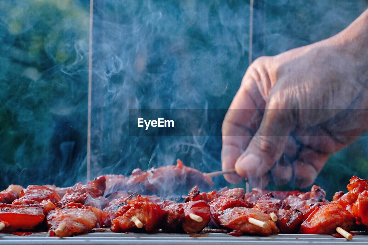 food and drink, food, meat, barbecue grill, barbecue, preparation, human hand, freshness, hand, human body part, grilled, heat - temperature, preparing food, one person, smoke - physical structure, unrecognizable person, day, real people, holding, outdoors, finger, dinner, chef