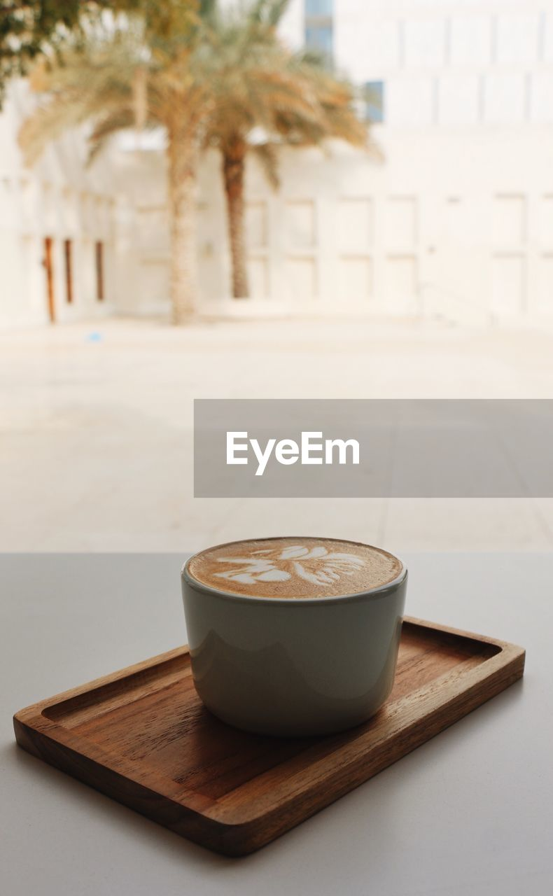 table, food and drink, drink, refreshment, focus on foreground, coffee - drink, coffee, architecture, cup, mug, still life, coffee cup, no people, freshness, hot drink, indoors, frothy drink, built structure, wood - material, food, non-alcoholic beverage, latte, crockery