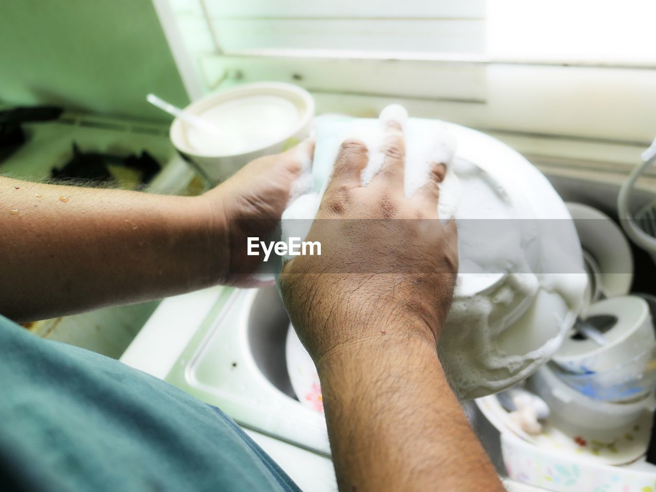 Over the shoulder view of man washing utensils in sink at home