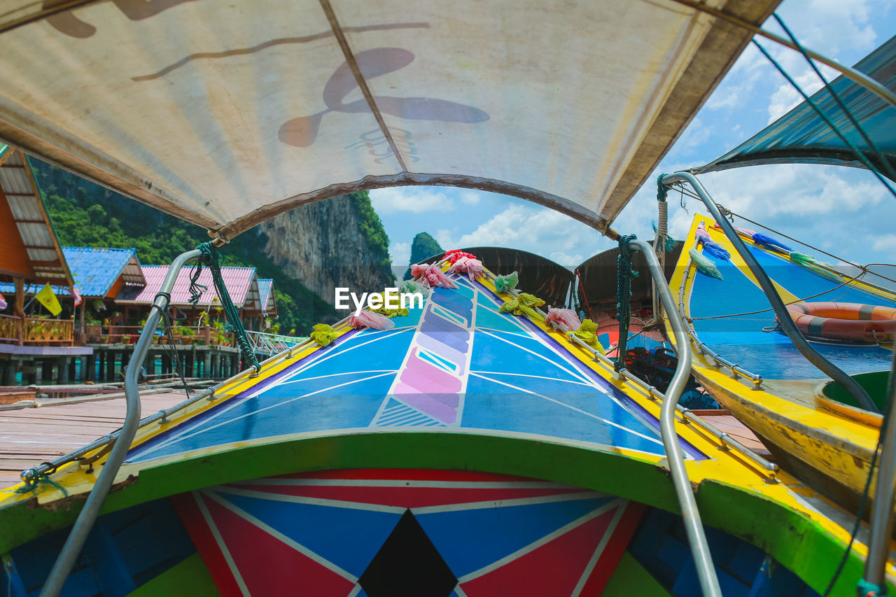 day, leisure activity, real people, amusement park, multi colored, men, nature, people, amusement park ride, outdoors, built structure, childhood, group of people, sky, architecture, arts culture and entertainment, lifestyles, fun, transportation, water