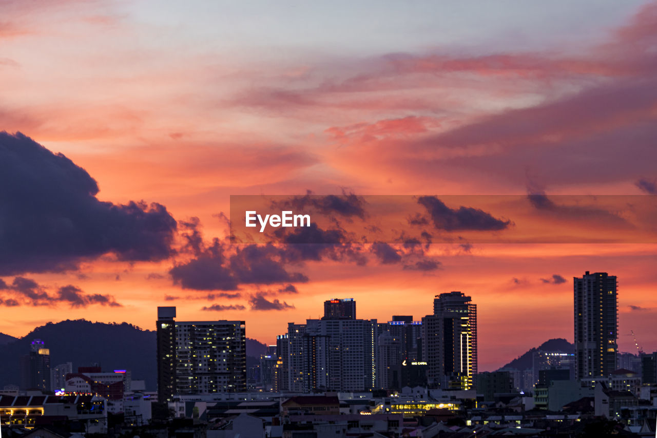 building exterior, sunset, architecture, built structure, sky, city, cloud - sky, building, orange color, cityscape, nature, office building exterior, no people, skyscraper, residential district, tall - high, urban skyline, beauty in nature, outdoors, modern, settlement, financial district, romantic sky