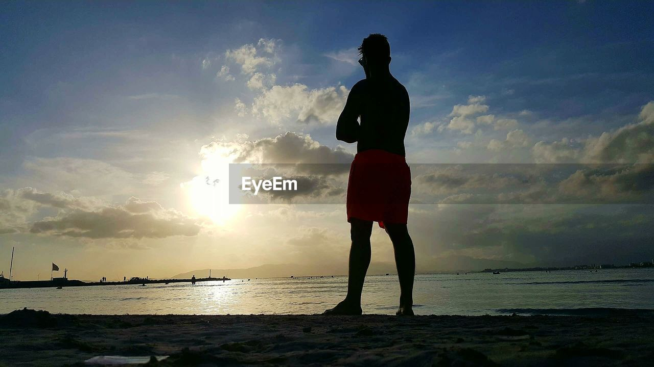 sea, sunset, silhouette, sky, water, beach, one person, standing, horizon over water, cloud - sky, nature, real people, full length, rear view, sun, beauty in nature, scenics, tranquil scene, outdoors, leisure activity, tranquility, lifestyles, men, day, people