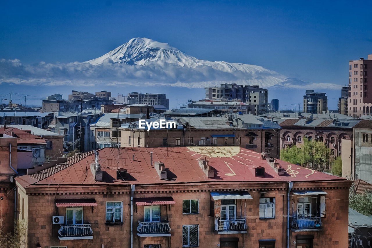 Cityscape Against Snowcapped Mountain