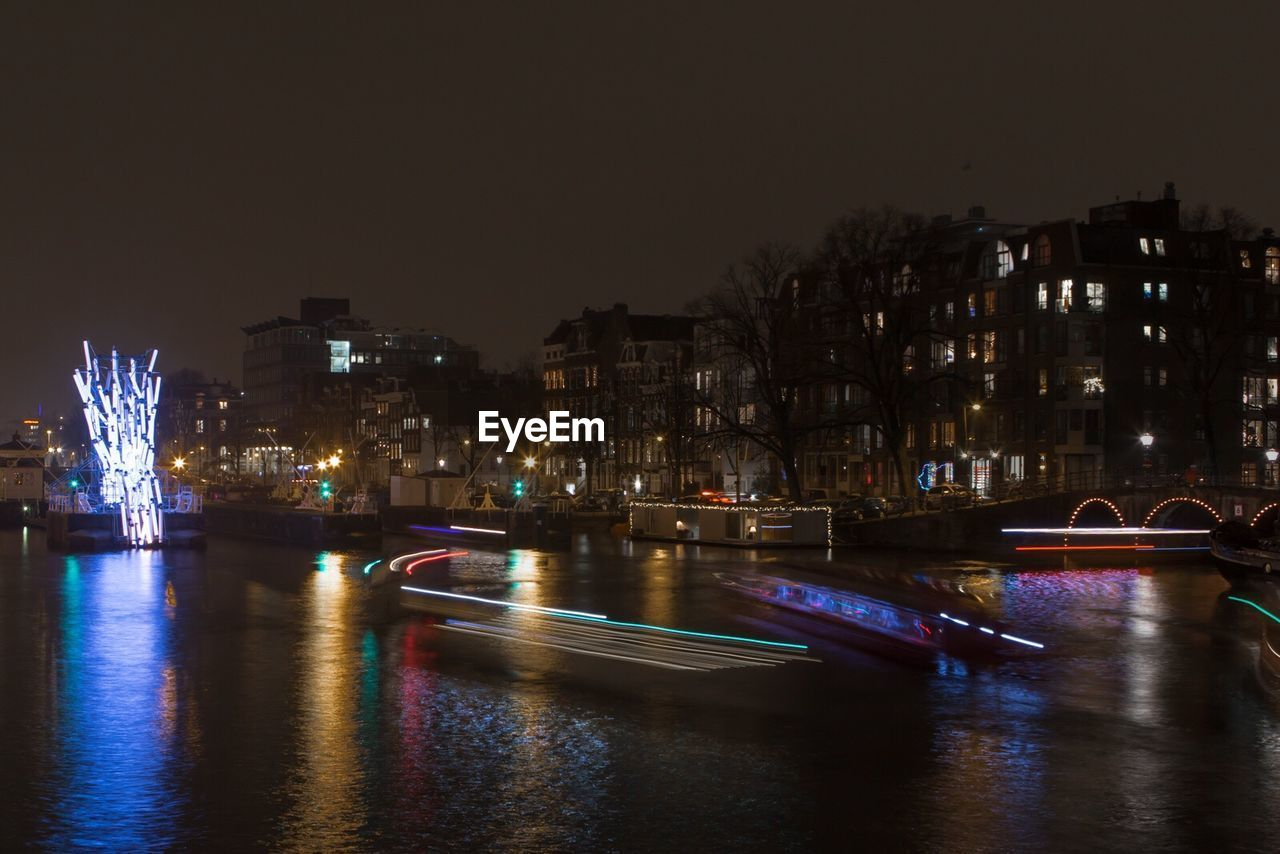 night, illuminated, architecture, built structure, building exterior, city, water, river, waterfront, transportation, no people, cityscape, light trail, travel destinations, outdoors, nautical vessel, sky