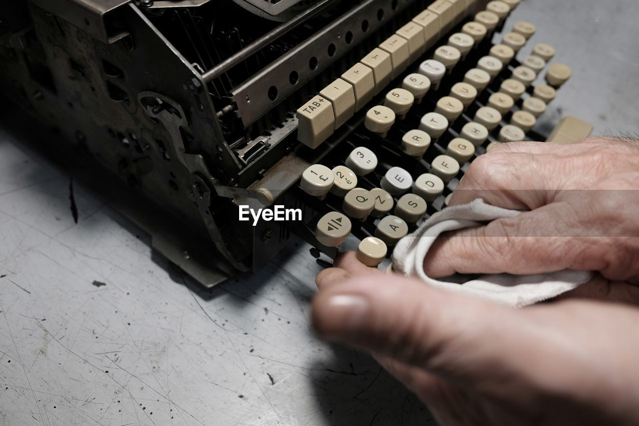 Close-Up Of Person Cleaning Typewriter On Table