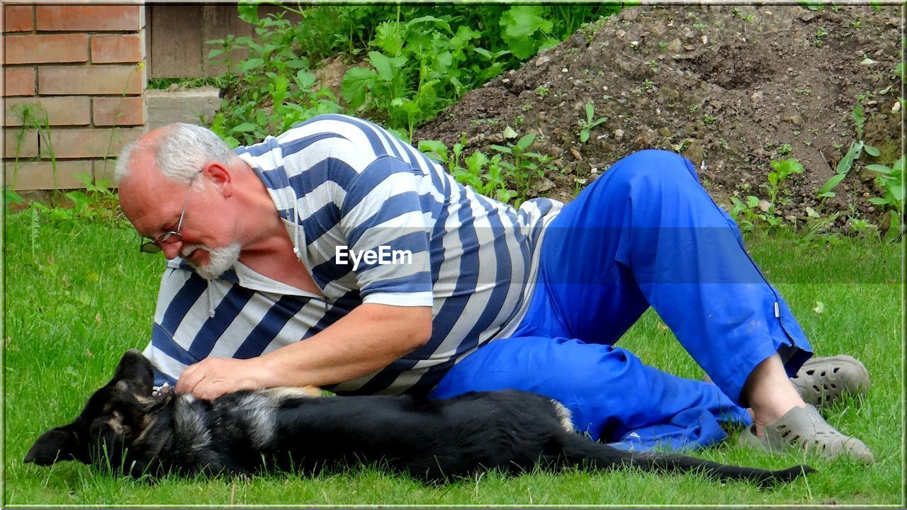 Full Length Of Senior Man Playing With Dog Lying On Grassy Field