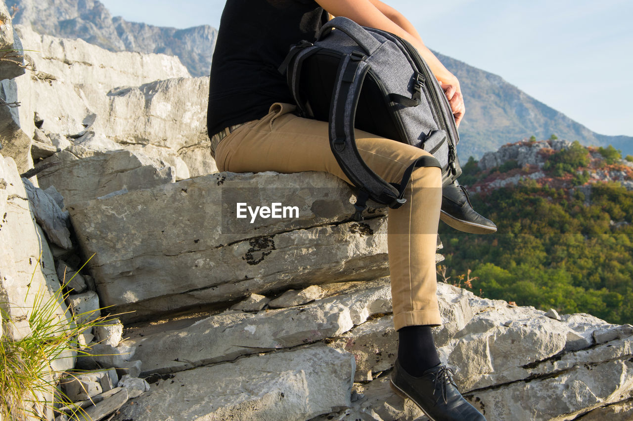 real people, mountain, one person, lifestyles, leisure activity, low section, day, nature, human leg, human body part, adventure, solid, body part, activity, outdoors, casual clothing, hiking, climbing, rock