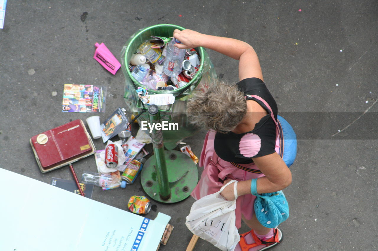 High Angle View Of Woman Throwing Bottle In Garbage Bin On Street