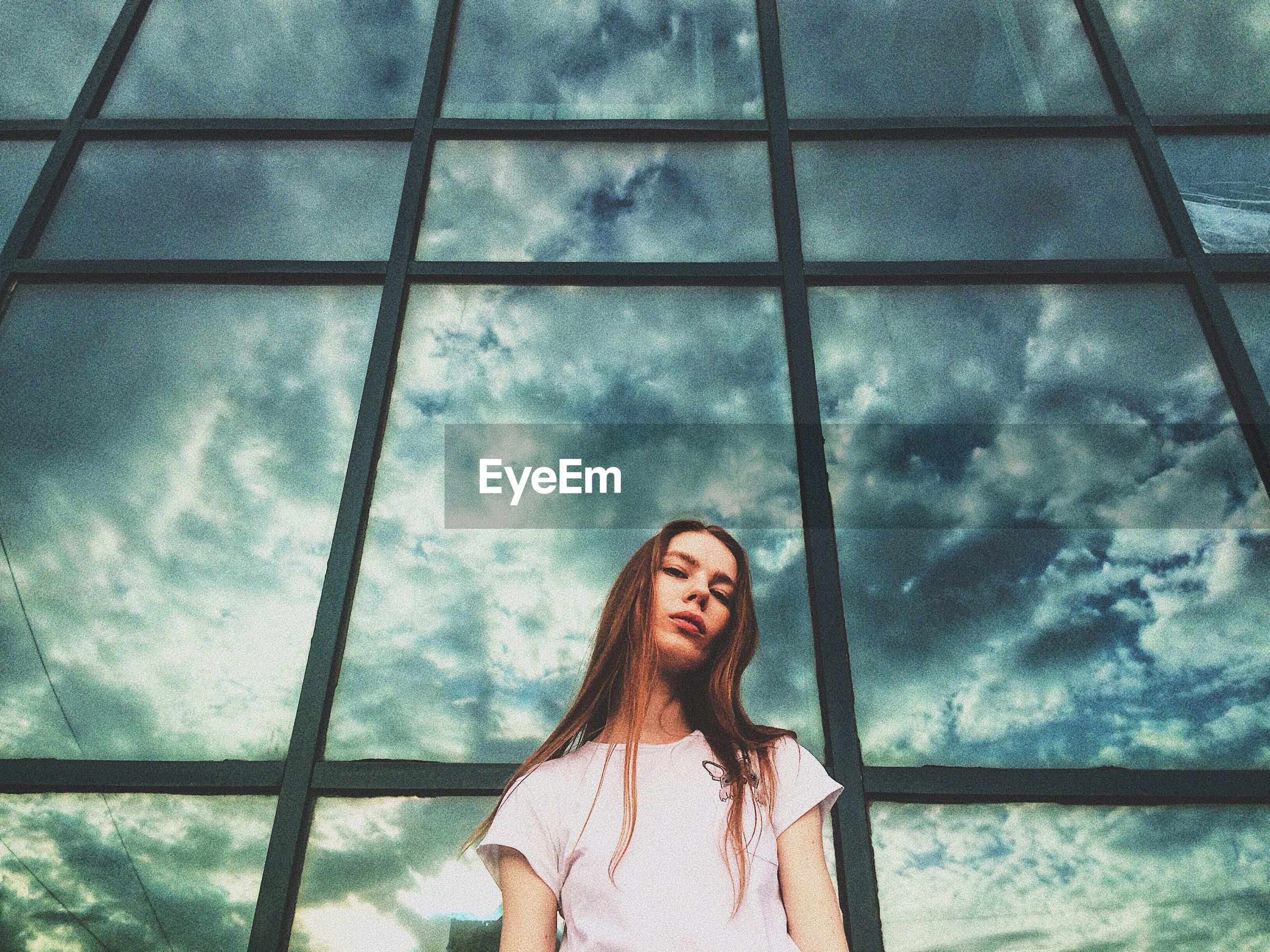 Low angle portrait of young woman against glass window with cloudy sky in background