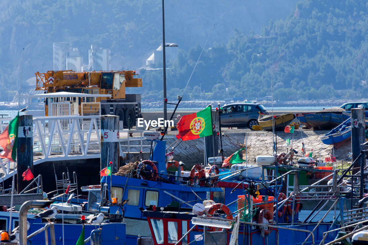 transportation, mode of transportation, water, nautical vessel, day, nature, flag, mountain, architecture, harbor, outdoors, no people, built structure, sea, building exterior, pier, travel, sky, moored, sailboat