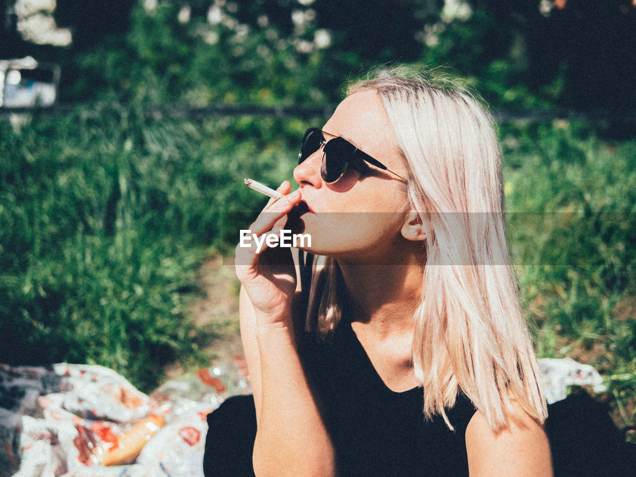 Close-Up Of Beautiful Woman Smoking On Field