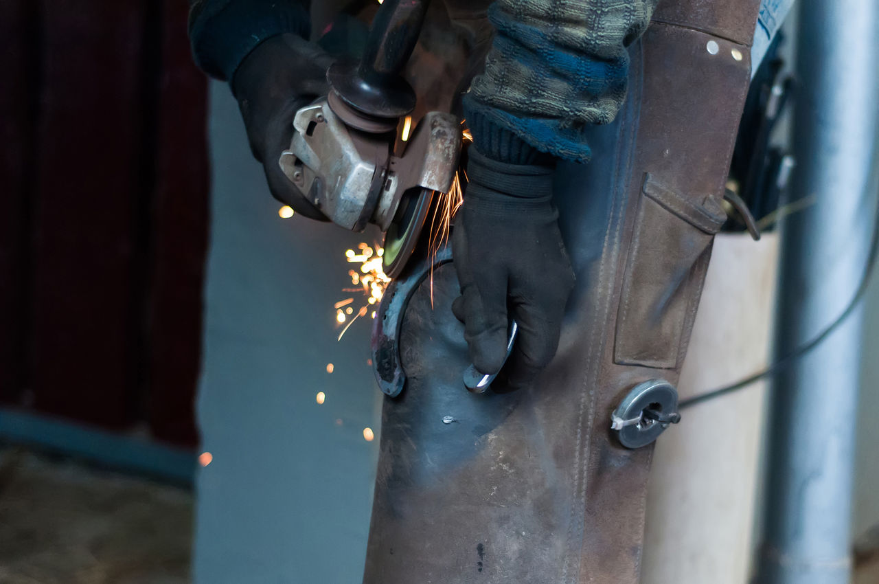 one person, real people, working, midsection, occupation, human body part, metal, hand, holding, selective focus, human hand, low section, day, standing, outdoors, focus on foreground, protective glove, work tool, men, metal industry