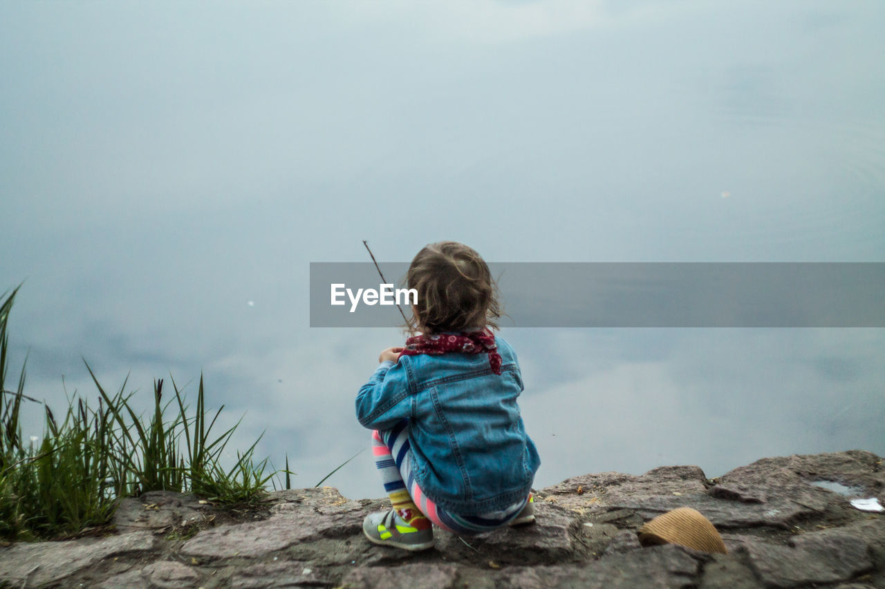Rear View Of Girl Sitting On Rock Against Cloudy Sky