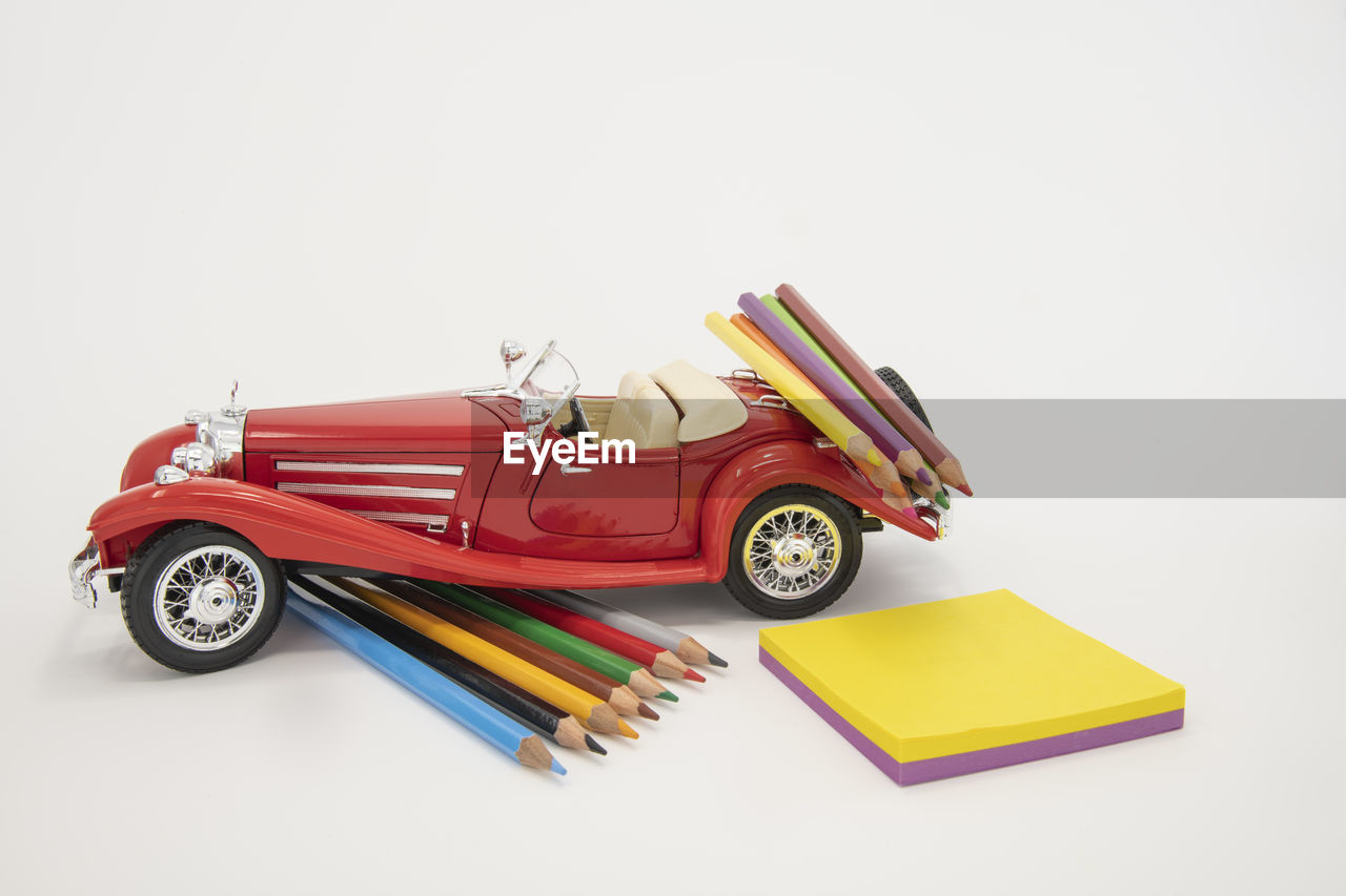 studio shot, white background, still life, indoors, copy space, toy car, toy, no people, car, red, cut out, high angle view, multi colored, transportation, close-up, mode of transportation, education, yellow