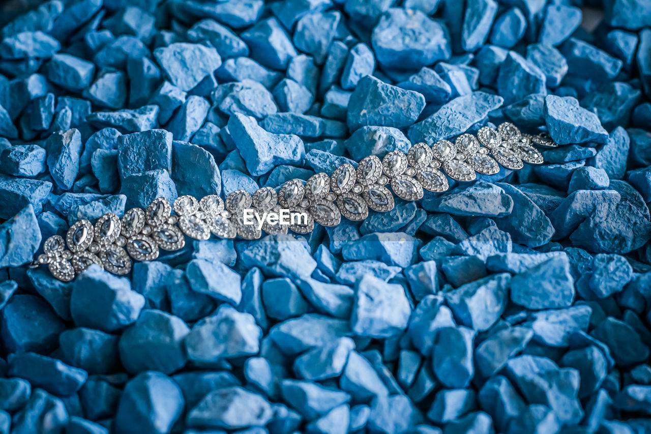 High angle view of diamond necklace on stones